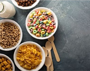 Five bowls of breakfast cereal with wooden spoons on gray slate table